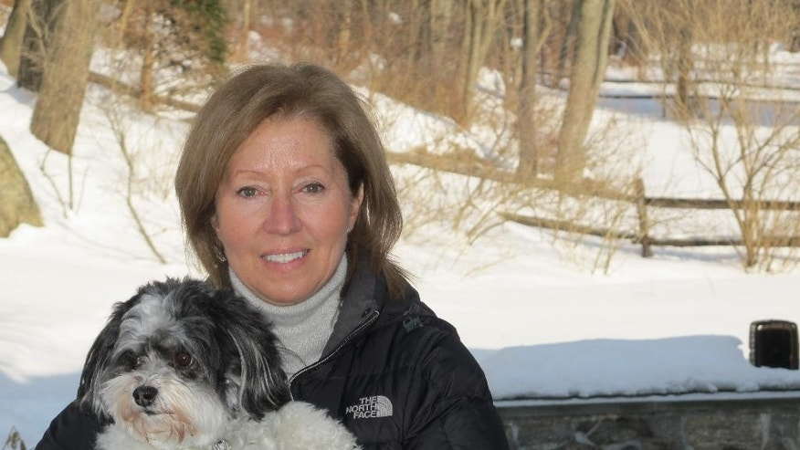 In this Feb. 19, 2015 photo, Ann Styles Brochstein holds her Havanese dog Samson near where Samson was attacked by a coyote outside her home in Chappaqua, N.Y. The suburban Town of New Castle, which includes Chappaqua, is divided over how to deal with the coyotes that have moved in over the last several years. (AP Photo/Jim Fitzgerald)