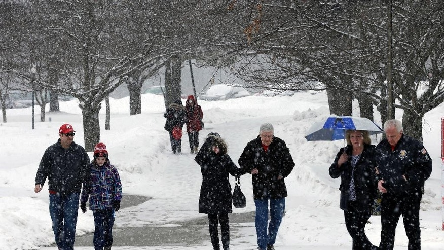 People walk in falling snow Sunday, March 1, 2015, in Piscataway, N.J. The National Weather Service has issued a winter storm warning for most of central and southern New Jersey, while the rest of the state is under winter weather advisory. Forecasters say a wintry mix of snow, sleet, freezing rain and rain started falling across the state late Sunday morning and should continue through early Monday. (AP Photo/Mel Evans)