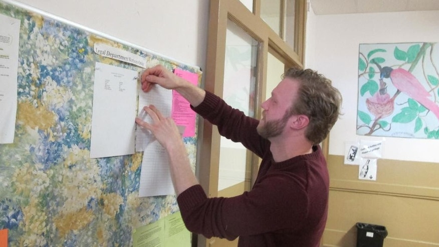 In a Jan. 15, 2015 photo, legal assistant Jake Steinmetz posts information on the bulletin board of Vive La Casa in Buffalo, N.Y. The shelter, which helps refugees seek asylum in Canada and the United States, announced it  is being purchased by fellow Buffalo nonprofit Jericho Road Community Health Center, which will continue the shelter's mission. (AP Photo/Carolyn Thompson)