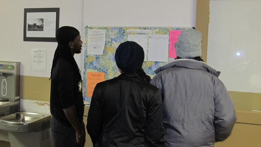 In a Jan. 15, 2015 photo, asylum-seekers staying at the Vive La Casa shelter in Buffalo, N.Y., check to see whether they have been scheduled for an interview with Canadian immigration officials the following day. The shelter, which has helped refugees seek asylum in Canada and the United States for 30 years, is being purchased by another Buffalo nonprofit, Jericho Road Community Health Center, which will continue its work. (AP Photo/Carolyn Thompson)
