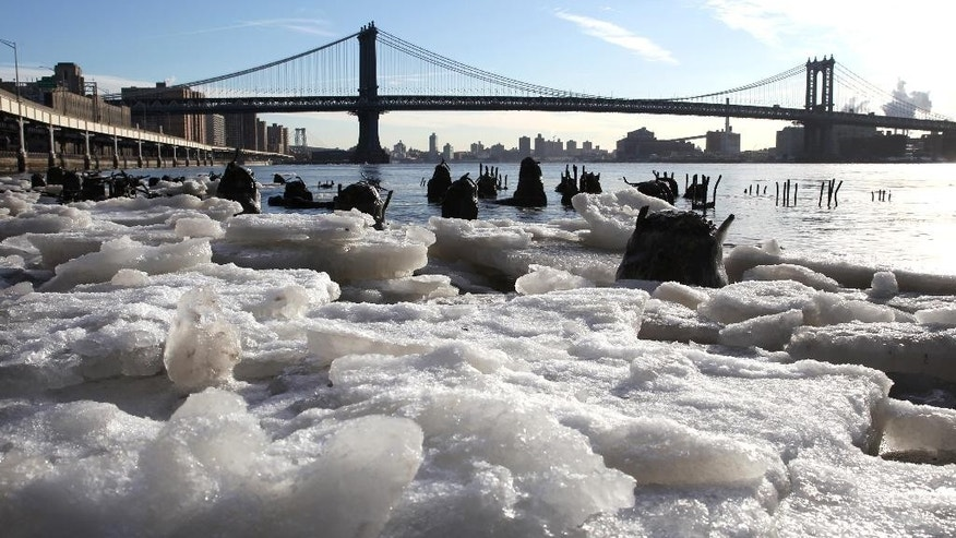 FILE - In this Feb. 16, 2015 file photo, ice forms along the shore of the Manhattan side of the East River in New York where temperatures in the city were in the single digits. For many cities in the Northeast, it was the coldest February on record, and some places recorded the most days of zero or below temperatures. The Manhattan Bridge is in the background. (AP Photo/Peter Morgan, File)