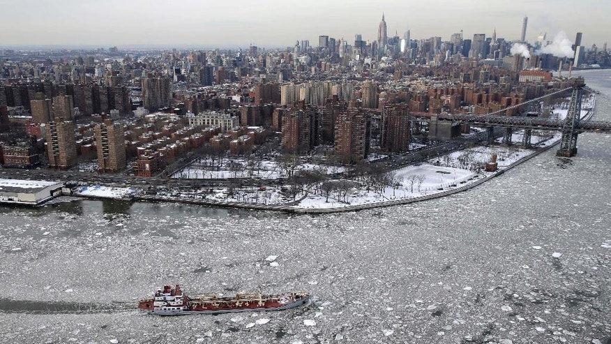 FILE - In this Feb. 24, 2015 file photo, a boat makes its way through ice on the East River in New York. For many cities in the Northeast, it was the coldest February on record, and some places recorded the most days of zero or below temperatures. (AP Photo/Seth Wenig, File)