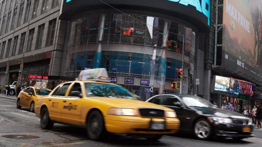 FILE - In this May 16, 2012 file photo, a taxi passes in front of the Nasdaq MarketSite in New York's Times Square. After fifteen long years, the Nasdaq is close to topping its all-time high of 5,048.62, set on March 10, 2000. (AP Photo/Richard Drew, File)