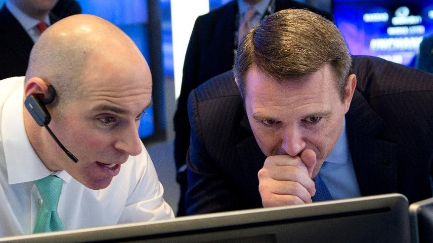 FILE - In this Feb. 12, 2015 file photo, Jay Heller, IPO Execution Officer for Nasdaq, left, shows Keith Dunleavy, CEO of Inovalon, the progress of pricing for his company's stock on computer screens during the Bowie, Maryland health-tech firm's IPO at the Nasdaq MarketSite in New York. After fifteen long years, the Nasdaq is close to topping its all-time high of 5,048.62, set on March 10, 2000.  (AP Photo/Mark Lennihan, File)