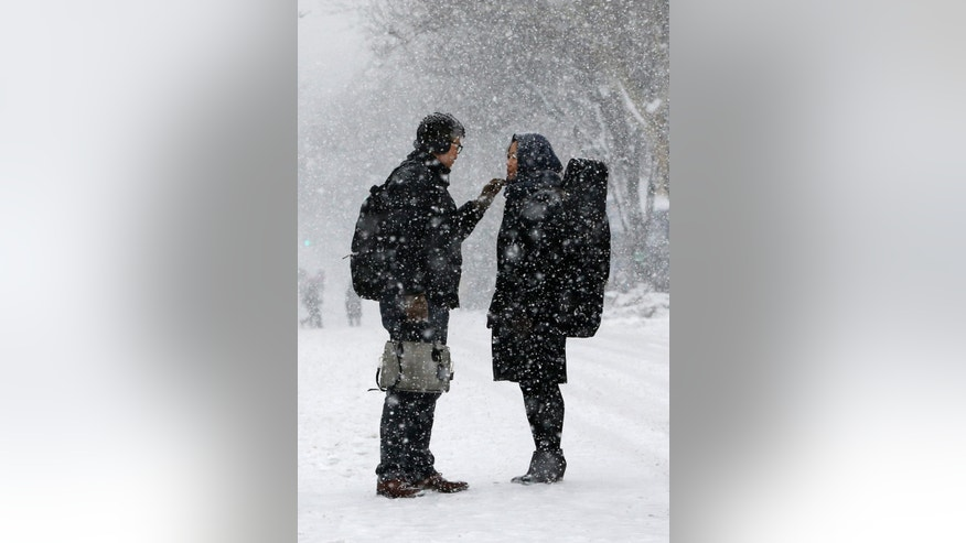 Min Park pauses to brush snow off his wife Michelle's face as the pair walk down a closed street in the Sunnyside, Queens neighborhood of New York, Sunday, March 1, 2015. The street was closed due to an earlier parade. (AP Photo/Kathy Willens)