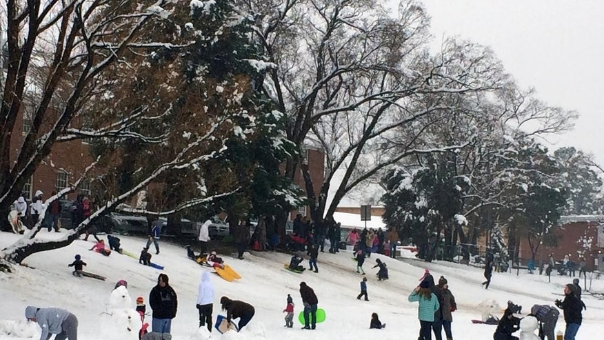 People play in the snow in Flagstaff, Ariz., Sunday, March 1, 2015. Snow and rain soaked parts of northern and central Arizona on Sunday, while a storm in California began to drift into the state's southern region. (AP Photo/Felicia Fonseca)