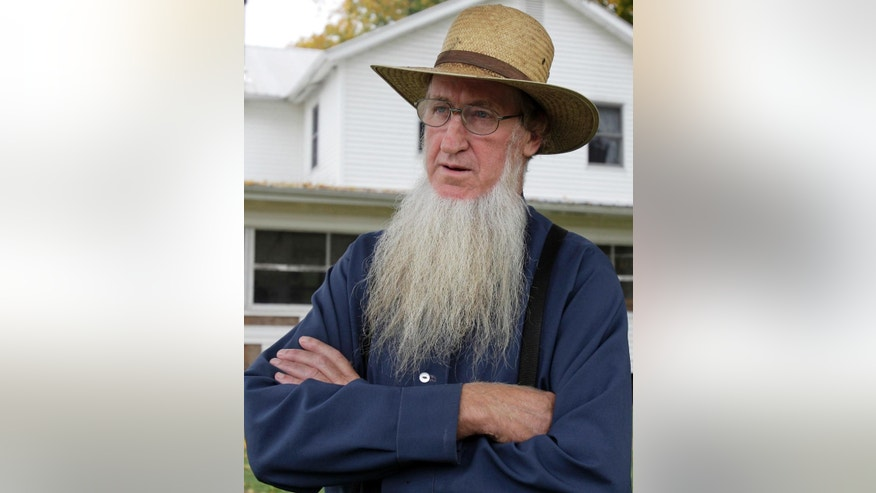 FILE - In this Oct. 10, 2011 file photo, Sam Mullet Sr. stands in the front yard of his home in Bergholz, Ohio. Sixteen members of a breakaway Amish community from eastern Ohio are scheduled to be resentenced in Cleveland after a federal appellate court overturned their hate crime convictions. The resentencing Monday, March, 2, 2015, is needed because the original sentences for the 16 didn't distinguish between their hate crimes convictions and convictions on other charges related to the forced cutting of beards and hair of seven people. All were members of other Ohio Amish communities. Eight of the 16 already have served their sentences and can't be returned to prison.  (AP Photo/Amy Sancetta, File)