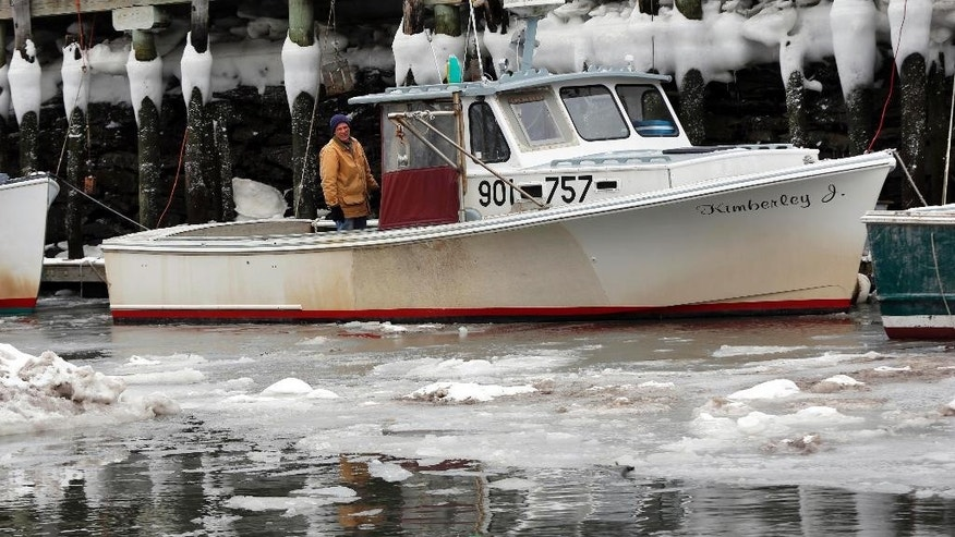 In this Thursday, Feb. 26, 2015 photo, a lobsterman looks out at the icy waters while checking on the condition of his boat in Portland, Maine. Ice clings to pilings at the high-tide mark in the background. Portland Harbor is encountering more ice than it has in years thanks to the coldest February on record. (AP Photo/Robert F. Bukaty)