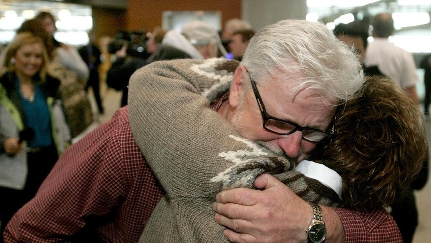Freed aid worker Arlynn Hefta embraces his wife at Hector International Airport, Tuesday, March 3, 2015 in Fargo, N.D. Hefta was among four American missionaries who were released after several days of detention and questioning by Venezuelan authorities. (AP Photo/Bruce Crummy)