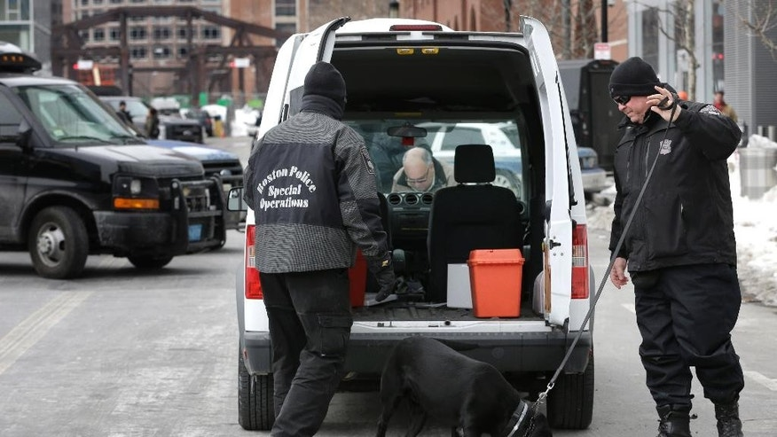 Boston Police Special Operations officers use a bomb-sniffing dog while searching a vehicle on a street near the federal courthouse, in Boston, Tuesday, March 3, 2015. A panel of 12 jurors and six alternates was seated Tuesday after two months of jury selection for the federal death penalty trial of Boston Marathon bombing suspect Dzhokhar Tsarnaev. (AP Photo/Steven Senne)
