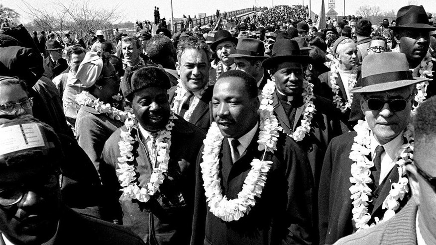 FILE - In this March 21, 1965 file photo, Martin Luther King, Jr. and his civil rights marchers cross the Edmund Pettus Bridge in Selma, Ala., heading for capitol, Montgomery, during a five day, 50 mile walk to protest voting laws. The Edmund Pettus Bridge gained instant immortality as a civil rights landmark when white police beat demonstrators marching for black voting rights 50 years ago this week in Selma, Alabama. What's less known is that the bridge is named for a reputed leader of the early Ku Klux Klan. Now, a student group wants to rename the bridge that will be the backdrop when President Barack Obama visits Selma on Saturday, March 7, 2015.  (AP Photo/File)
