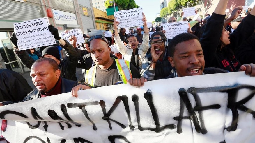 Protestors rally in downtown Los Angeles, against a police shooting of a homeless man on Tuesday, March 3, 2015. Several dozen people rallied in protest of the shooting, which came amid lingering tensions in the U.S. over the police killings of unarmed black men in Missouri and New York City.  (AP Photo/Nick Ut)