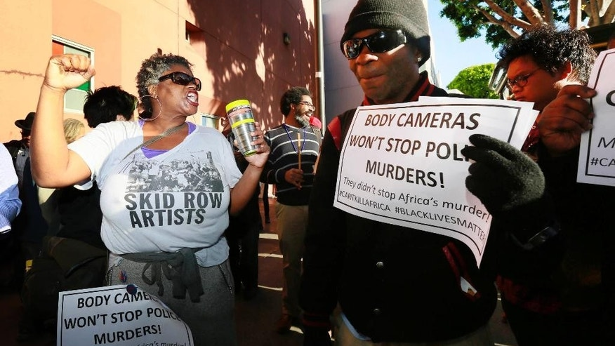 Suzette Shaw, left, a homeless woman, joins others protesting a police shooting of a homeless man on Tuesday, March 3, 2015, in downtown Los Angeles. There was a moment of silence at the site of the shooting where several dozen people rallied Tuesday in protest. The group then marched toward the downtown police administration building, the site of a meeting of the city Police Commission, a panel of civilians who oversee the Police Department. (AP Photo/Nick Ut)