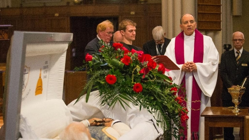 Rev. Peter Rocca prays over the body of Rev. Theodore Hesburgh at the beginning of the visitation on Tuesday, March 3, 2015, inside the Sacred Heart Basilica at the University of Notre Dame in South Bend, Ind.  Thousands of students, alumni and admirers are expected on the University of Notre Dame campus Tuesday to pay their respects to the Rev. Theodore Hesburgh, who served as the school's president for 35 years while also promoting human rights. Hesburgh died Thursday, Feb. 26, 2015. He was at 97. (AP Photo/South Bend Tribune, Robert Franklin, Pool)
