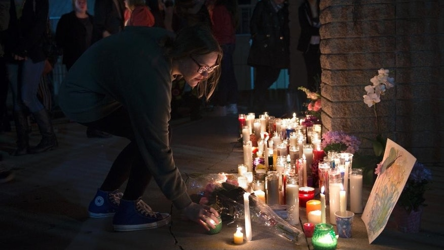 CJ Holton places her candle during a candlelight vigil for Jillian Jacobson in front of El Dorado High School on Monday, March 2, 2015 in Placentia, Calif.  Jacobson, a teacher, committed suicide by hanging herself in her classroom. Students arriving at school found Jacobson's classroom door locked, Placentia police Lt. Eric Point said. Thinking she was late, they went next door to get another teacher, who returned with them and opened the door. Jacobson was found hanging from the ceiling. (AP Photo/The Orange County Register, Matt Masin)    MAGS OUT; LOS ANGELES TIMES OUT