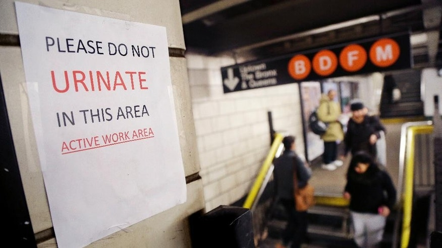 "A sign hangs in the West 4th Street subway station reads ""Please Do Not Urinate In This Area - Active Work Area,"" Tuesday, March 3, 2015 in New York. The sign was posted by workers who are doing track work. ""That station is an area that is notorious for public urination,"" said Kevin Ortiz, a spokesman for the agency that operates the system. Greenwich Village night-life patrons, homeless people and others all seem drawn to relieve themselves there, he added. (AP Photo/Mark Lennihan)"