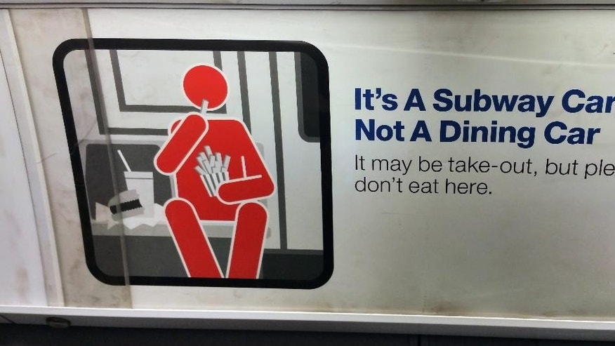 "A placard running along the interior of a New York City subway car reminds passengers that they are in a ""Subway Car, Not A Dining Car,"" as a subway travels below the streets of New York City, Wednesday, March 4, 2015. New York's Metropolitan Transportation Authority has launched a new campaign that points out some common but rude practices by their ridership and asks them to be more considerate of their fellow passengers. (AP Photo/Verena Dobnik)"