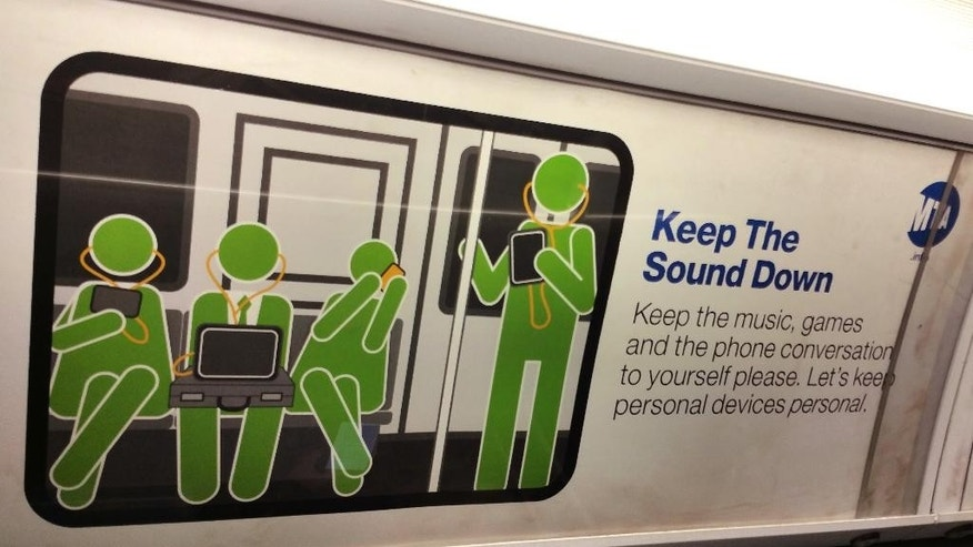 """Keep the sound down,"" reads a placard in a subway car travelling beneath the streets of New York City, Wednesday, March 4, 2015. The New York Metropolitan Transportation Authority has launched a campaign extorting their riders to be more considerate of each other. The MTA, which oversees a subway system that transports about 6 million riders every weekday, began putting its signs in the subways in late 2014 after it received numerous complaints from riders about such things as space hogging, passengers eating pungent foods during their commute and others grooming themselves. (AP Photo/Verena Dobnik)"