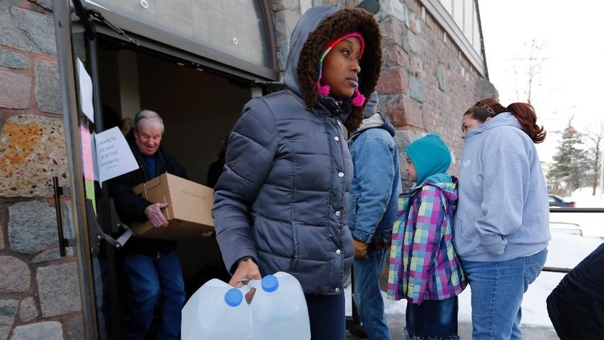 In this Tuesday, Feb. 3, 2015 photo, Genetha Campbell carries free water being distributed at the Lincoln Park United Methodist Church in Flint, Mich, Since the financially struggling city broke away from the Detroit water system last year, residents have been unhappy with the smell, taste and appearance of water from the city's river as they await the completion of a pipe to Lake Huron. They also have raised health concerns, reporting rashes, hair loss and other problems. A General Motors plant stopped using the water, saying it was rusting its parts. (AP Photo/Paul Sancya)