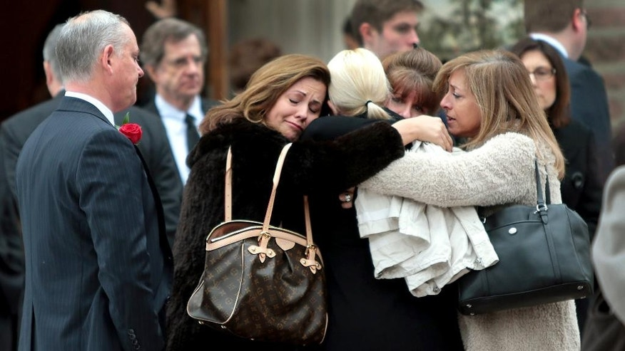 Family members of Missouri State Auditor Tom Schweich embrace outside The Church of St. Michael and St. George in Clayton, Mo., after his funeral on Tuesday, March 3, 2015. Schweich, 54, fatally shot himself last Thursday in what police say was an apparent suicide at his home in Clayton. (AP Photo/St. Louis Post-Dispatch, Robert Cohen, Pool)