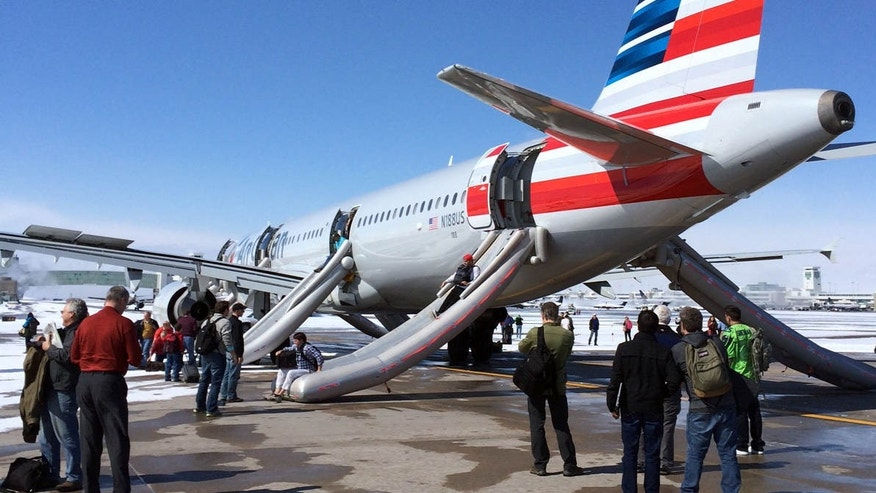 March 4, 2015:  Long passengers slide down emergency chutes after an American Airlines flight from Charlotte, N.C., soon after landing in Denver.
