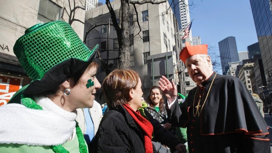 FILE- In this March 19, 2009 file photo, Cardinal Edward Egan speaks with a couple of women along the route of the St. Patrick's Day Parade 2009, in New York. Egan, the former archbishop of New York, died of cardiac arrest Thursday, March 5, 2015, in New York. He was 82. (AP Photo/Frank Franklin II, File)