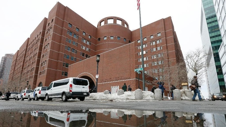 The John Joseph Moakley United States Courthouse is reflected in melted snow, Wednesday, March 4, 2015, in Boston, on the first day of the federal death penalty trial of Boston Marathon bombing suspect Dzhokhar Tsarnaev. Tsarnaev is charged with conspiring with his brother to place two bombs near the marathon finish line in April 2013, killing three and injuring 260 people. (AP Photo/Michael Dwyer)