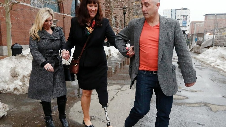 Boston Marathon bombing survivors Heather Abbott, left, and Karen Rand, center, are escorted from federal court, Wednesday, March 4, 2015, in Boston, after the first day of the federal death penalty trial of Boston Marathon bombing suspect Dzhokhar Tsarnaev. Tsarnaev is charged with conspiring with his brother to place two bombs near the marathon finish line in April 2013, killing three and injuring 260 people. (AP Photo/Michael Dwyer)