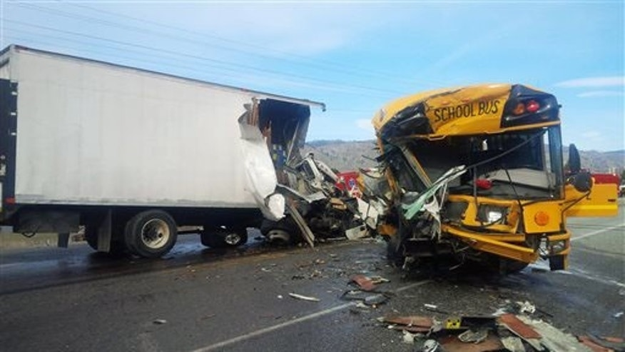 This photo shows the scene of an accident in which a motorist was killed and five students and others were injured in a crash involving a school bus, box truck and car near Orondo in Central Washington state.