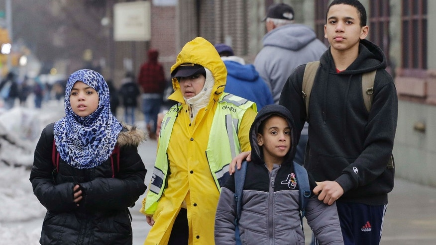 A crossing guard assists three Muslim school children at the end of a school day.