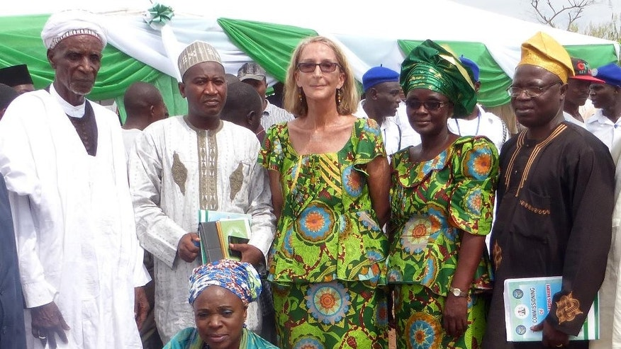 FILE - In this undated file photo provided by Mike Henry, Seattle missionary Rev. Phyllis Sortor, center, stands with a delegation of area dignitaries in a town in Nigeria. The Free Methodist Church said Friday, March 6, 2015, that Sortor, who was abducted last month from a school in Nigeria, has been released and is safe. (AP Photo/Mike Henry, File)