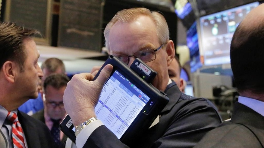 Trader Dennis Maguire works on the floor of the New York Stock Exchange, Friday, March 6, 2015. Stocks opened lower on Friday as another strong U.S. jobs report raised the likelihood that the Federal Reserve would start to raise interest rates later this year.  (AP Photo/Richard Drew)