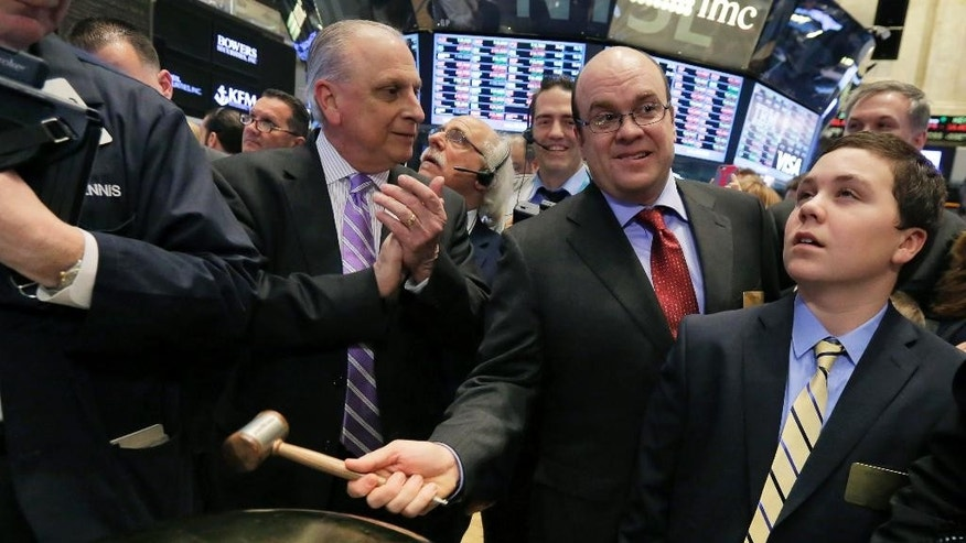 MaxPoint Interactive Chairman, President and CEO Joseph Epperson, second from right, joined by his son Michael Epperson, right, as he rings a ceremonial bell when his company's IPO to begin trading, on the floor of the New York Stock Exchange, Friday, March 6, 2015.  (AP Photo/Richard Drew)