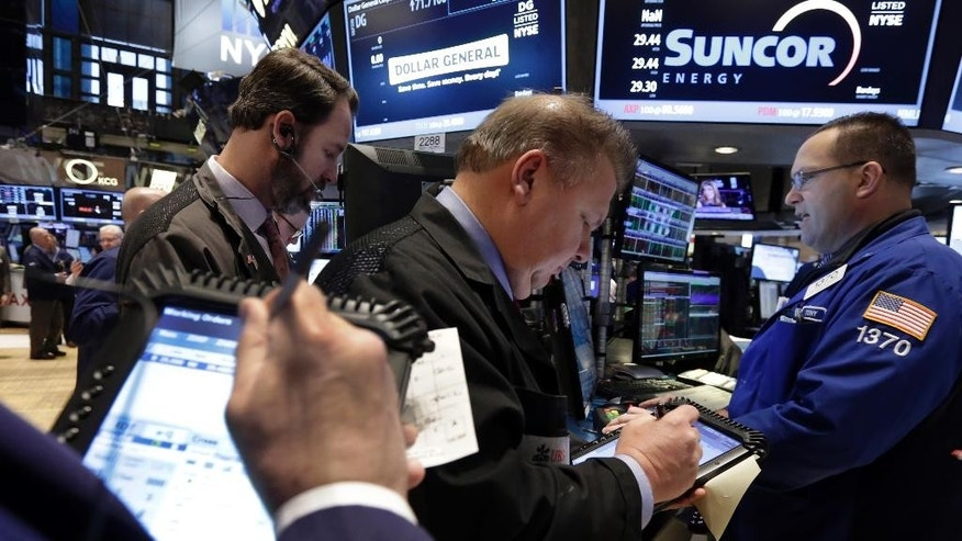 Traders gather at the post of specialist Anthony Matesic, right, on the floor of the New York Stock Exchange, Friday, March 6, 2015. Stocks opened lower on Friday as another strong U.S. jobs report raised the likelihood that the Federal Reserve would start to raise interest rates later this year. (AP Photo/Richard Drew)