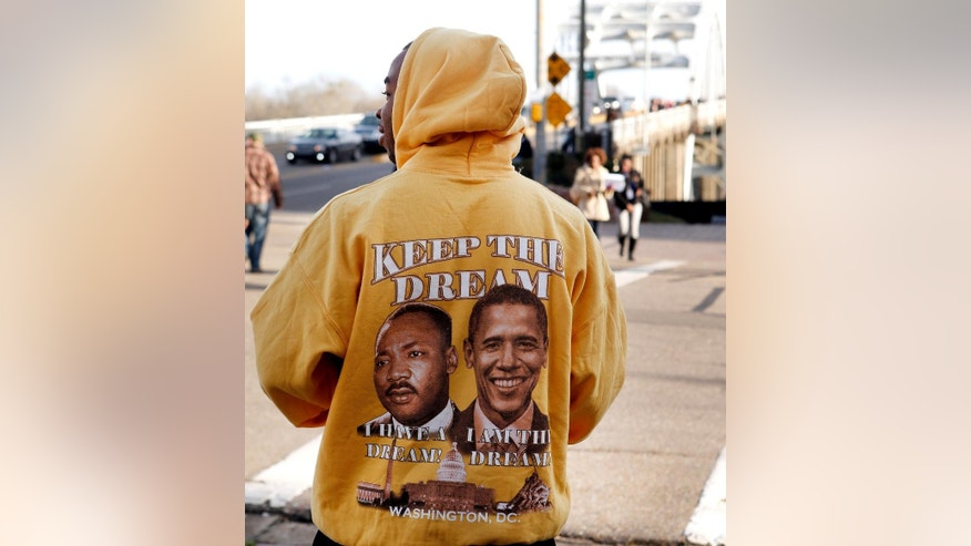 "A man passes out programs wearing a ""Keep The Dream,"" jacket as setup begins for the 50th Anniversary March over the Edmund Pettus Bridge, Friday, March. 6, 2015, in Selma, Ala. This weekend marks the 50th anniversary of ""Bloody Sunday,"" a civil rights march in which protesters were beaten, trampled and tear-gassed by police at the Edmund Pettus Bridge in Selma, Ala. (AP Photo/Butch Dill)"