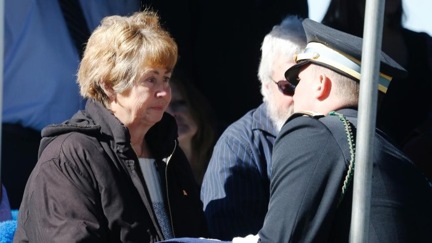Joann Mueller, left, niece of Korean War POW Floyd J.R. Jackson, accepts the flag that was draped over her uncle's casket from an honor guard member during a graveside service Saturday, March 7, 2015, in Centennial, Colo. The remains of Army Cpl. Jackson were returned to Colorado Thursday 64 years after he died in an enemy prisoner of war camp. (AP Photo/David Zalubowski)