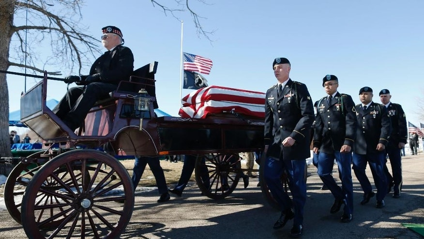 Flanked by members of an honor guard, a wagon carries the casket of Korean War POW Floyd J.R. Jackson Saturday, March 7, 2015, to a graveside service in Centennial, Colo. The remains of Army Cpl. Jackson were returned to Colorado Thursday,  64 years after he died in an enemy prisoner of war camp. (AP Photo/David Zalubowski)
