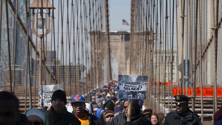 """Demonstrators march over the Brooklyn Bridge to mark the 50th anniversary of the landmark event of the civil rights movement in Selma, Ala., on Saturday, March 7, 2015, in New York.  Fifty years ago marchers crossing a bridge in Selma for a voting rights demonstration were beaten by police in a confrontation called """"Bloody Sunday."""" (AP Photo/John Minchillo)"""