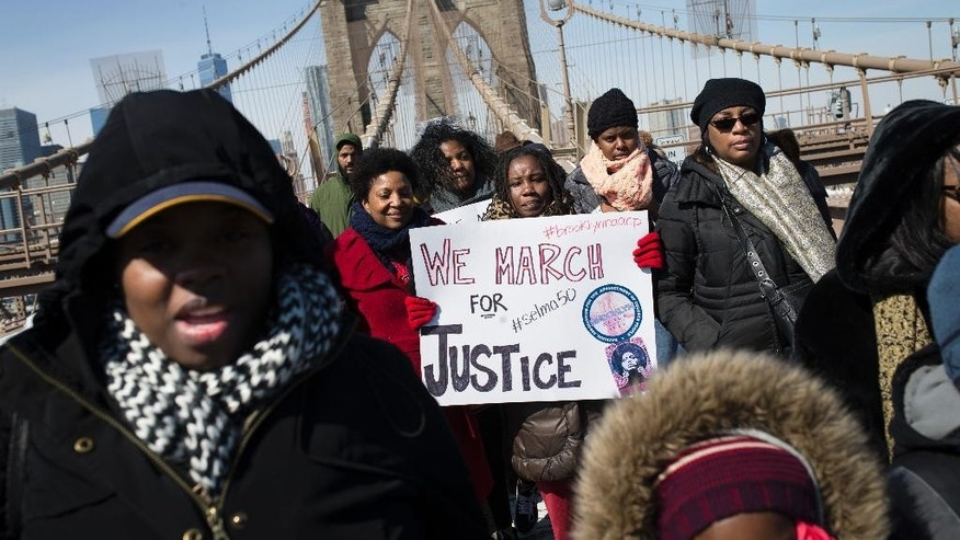 """Demonstrators march over the Brooklyn Bridge to mark the 50th anniversary of the landmark event of the civil rights movement in Selma, Ala., on Saturday, March 7, 2015, in New York.  Fifty years ago marchers crossing a bridge in Selma for a voting rights demonstration were beaten by police in a confrontation called """"Bloody Sunday.""""(AP Photo/John Minchillo)"""