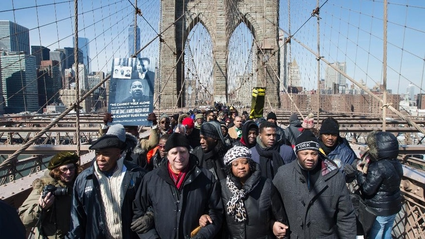 """From left, Brooklyn borough president Eric Adams, Civil rights attorney Norman Siegel, Dr. Karen Daughtry, and Senator Jesse Hamilton (D-NY), march over the Brooklyn Bridge to mark the 50th anniversary of the landmark event of the civil rights movement in Selma, Ala., on Saturday, March 7, 2015, in New York.  Fifty years ago marchers crossing a bridge in Selma for a voting rights demonstration were beaten by police in a confrontation called """"Bloody Sunday."""" (AP Photo/John Minchillo)"""