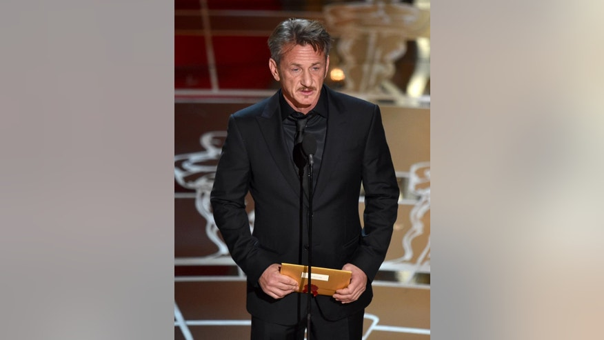 "FILE - In this Feb. 22, 2015 file photo, actor Sean Penn presents the award for best picture to Mexican-born Alejandro Iñárritu for his film, ""Birdman: Or (The Unexpected Virtue of Ignorance),"" at the Oscars at the Dolby Theatre in Los Angeles. On Saturday, March 7,  during a promotional tour for his new film ""The Gunman,"" in Beverly Hills, Penn opened up about the green card joke he made during the Oscars saying that he has ""absolutely no apologies"" for his comment. ""I found it hilarious,"" Iñárritu said after the ceremony. ""Sean and I have that kind of brutal (relationship) where only true friendship can survive."" Iñárritu directed Penn in the 2003 film ""21 Grams"" and the two remain close to this date. (Photo by John Shearer/Invision/AP, File)"