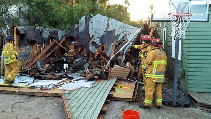 March 7, 2015: This photo provided by San Luis Obispo City Fire Department, City Fire Department personnel view the scene after a garage roof collapsed during an early St. Patrick's Day party near California Polytechnic State University in San Luis Obispo.