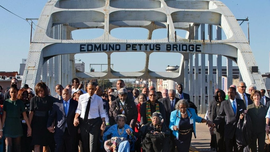 "March 7, 2015: President Barack Obama, fourth from left, walks holding hands with Amelia Boynton Robinson, who was beaten during ""Bloody Sunday,"" as they and the first family and others including Rep. John Lewis, D-Ga, left of Obama, walk across the Edmund Pettus Bridge in Selma, Ala,. for the 50th anniversary of the landmark event of the civil rights movement. (AP)"