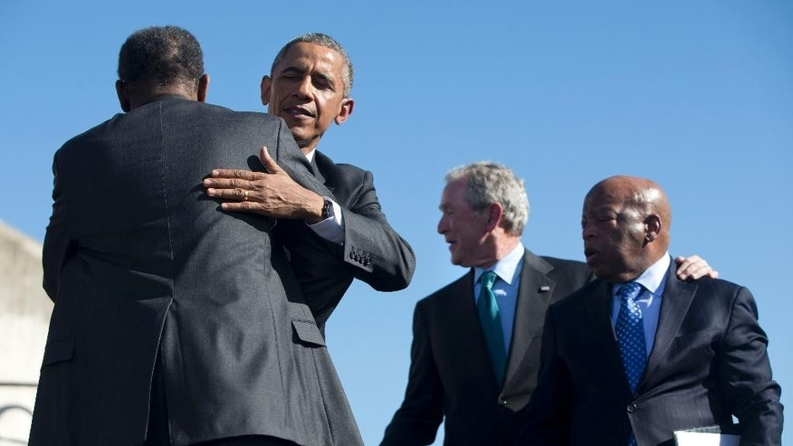 """President Barack Obama hugs Rev. Leodis Strong, Minister of Brown Chapel AME, after he said a closing prayer, while former President George W. Bush talks with Rep. John Lewis, D-Ga., by the Edmund Pettus Bridge in Selma, Ala., on the 50th anniversary of """"Bloody Sunday,"""" a landmark event of the civil rights movement, Saturday, March 7, 2015. (AP Photo/Jacquelyn Martin)"""