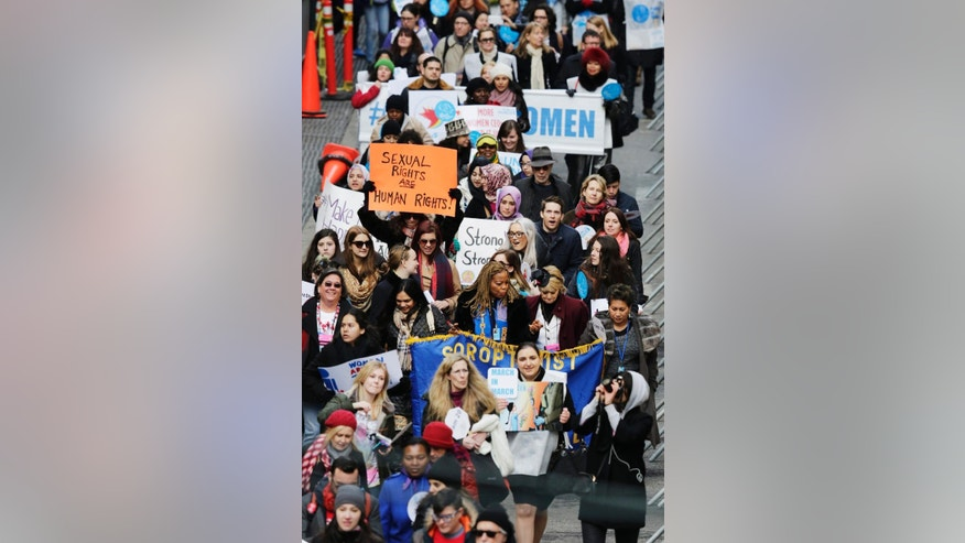 People walk in the International Women's Day march for gender equality and women's rights from the United Nations to Times Square, Sunday, March 8, 2015 in New York. About 1,000 people gathered to speak up for the gender that traditionally is paid less for work and often has a smaller voice in policy decisions. (AP Photo/Mark Lennihan)