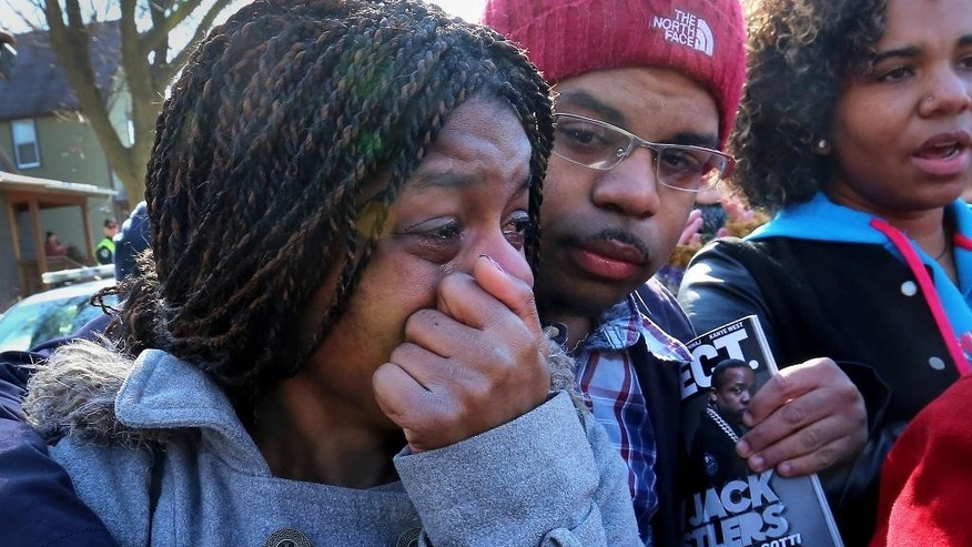 Kyrisha Isom, left, weeps with Derrick McCann during a rally protesting the shooting death of Tony Robinson, Saturday, March 7, 2015, in Madison, Wis. Robinson, an unarmed black 19-year-old, was fatally shot Friday by Matt Kenny, a white police officer, the Madison police chief said Saturday, March 7, 2015. Isom said she had been friends with Robinson for about 12 years. (AP Photo/Wisconsin State Journal, John Hart)
