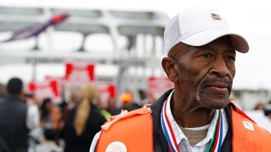 "John Rankin, an original marker from 1965, leads the way as they cross Edmund Pettus Bridge marching towards Montgomery Monday, March 9, 2015, in Selma, Ala., to mark the 50th anniversary of ""Bloody Sunday,"" a civil rights march in which protesters were beaten, trampled and tear-gassed by police at the Edmund Pettus Bridge in Selma, Ala. (AP Photo/Butch Dill)"