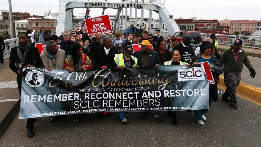 "People cross Edmund Pettus Bridge marching towards Montgomery, Monday, March 9, 2015, in Selma, Ala.to mark the 50th anniversary of ""Bloody Sunday,"" a civil rights march in which protesters were beaten, trampled and tear-gassed by police at the Edmund Pettus Bridge in Selma, Ala. (AP Photo/Butch Dill)"