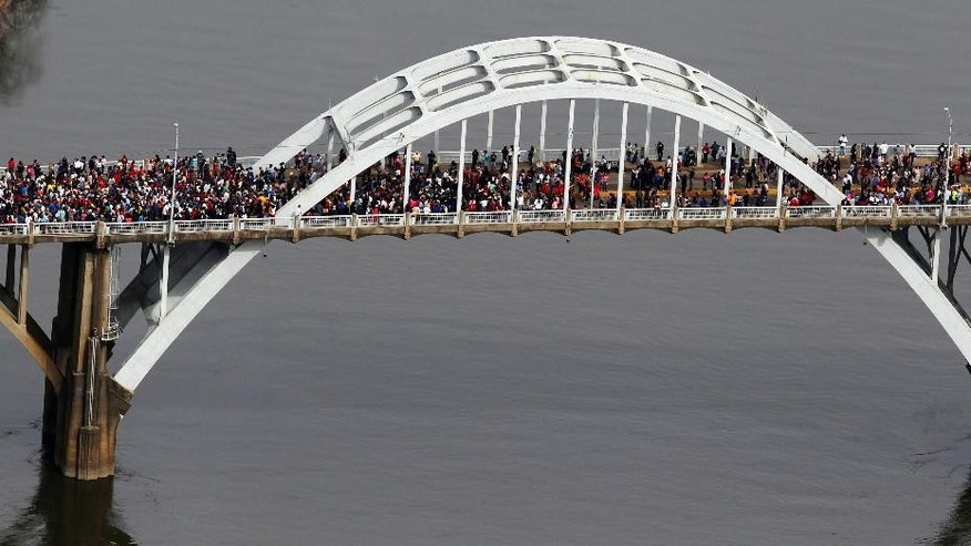 "In this aerial photo, crowds of people move in a symbolic walk across the Edmund Pettus Bridge, Sunday, March 8, 2015, in Selma, Ala. This weekend marks the 50th anniversary of ""Bloody Sunday,' a civil rights march in which protestors were beaten, trampled and tear-gassed by police at the Edmund Pettus Bridge, in Selma.  (AP Photo/Butch Dill)"
