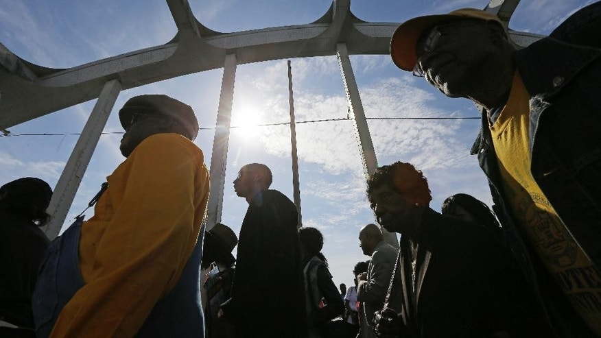 "Crowds of people walk toward Selma after taking a symbolic walk across the Edmund Pettus Bridge, Sunday, March 8, 2015, in Selma, Ala. This weekend marks the 50th anniversary of ""Bloody Sunday,"" a civil rights march in which protestors were beaten, trampled and tear-gassed by police at the Edmund Pettus Bridge, in Selma.  (AP Photo/Gerald Herbert)"